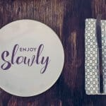 Enjoy slowly quote, healthy eating concept design with restaurant elements over retro style wood surface.
