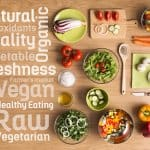 Creative vegetarian cooking at home with fresh healthy vegetables chopped, salads and kitchen wooden utensils, healthy eating text concepts on the left